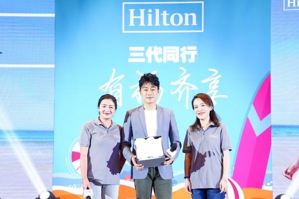 黄劼女士(左)代表希尔顿集团向佟大为先生赠送定制专属儿童浴袍